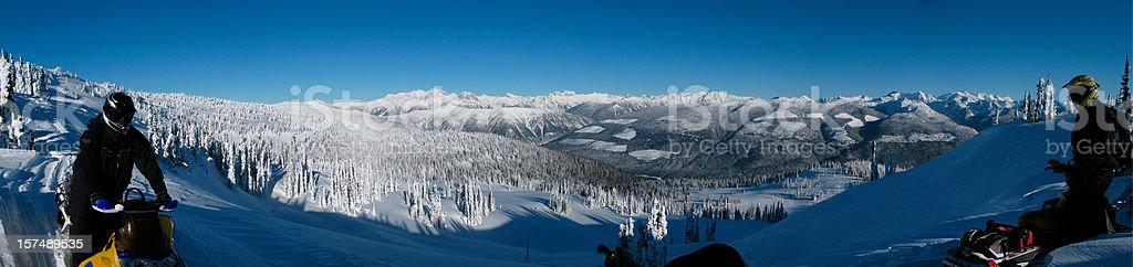 Panoramic Scenic British Columbia with two snowmobilers royalty-free stock photo