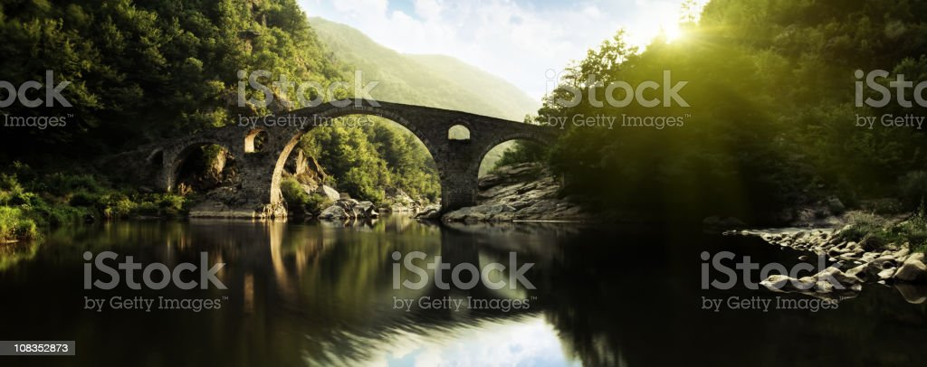 Panoramic shot of ancient bridge over river royalty-free stock photo
