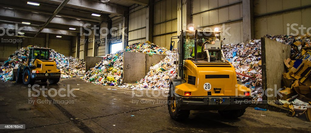 Panoramic shot of the earth movers in the garbage dump stock photo