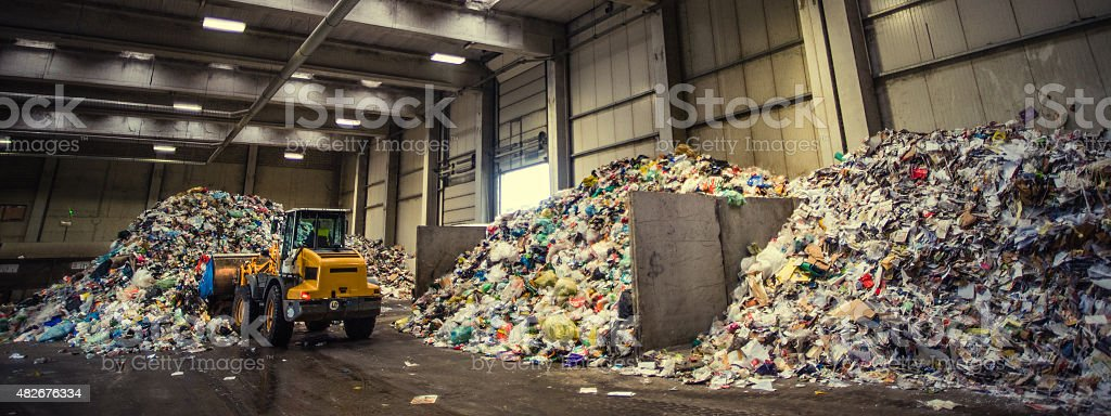 Panoramic shot of the excavator in the garbage dump stock photo