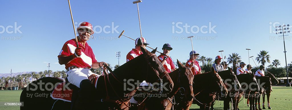 Panoramic shot polo players and umpire on horses at field royalty-free stock photo