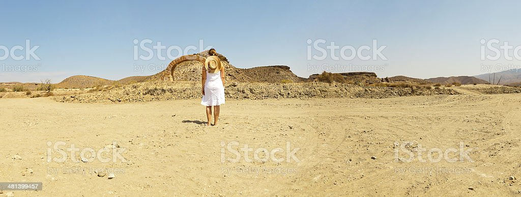 Panoramic shot woman with hat and dress in western town. stock photo
