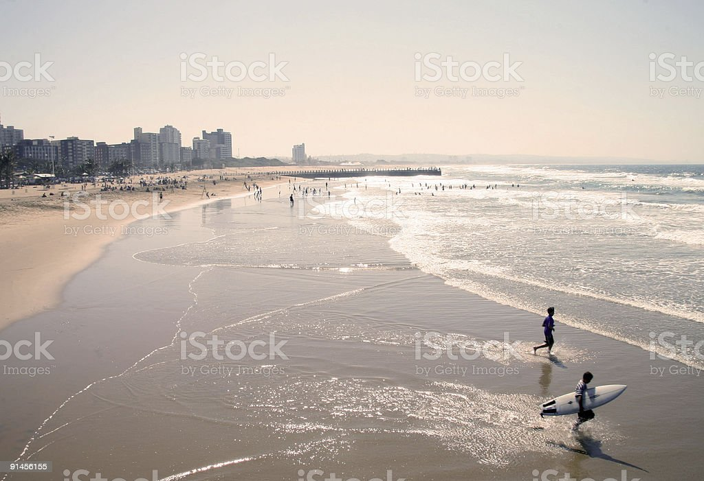 Panoramic view of a beach with surfers, people and buildings stock photo