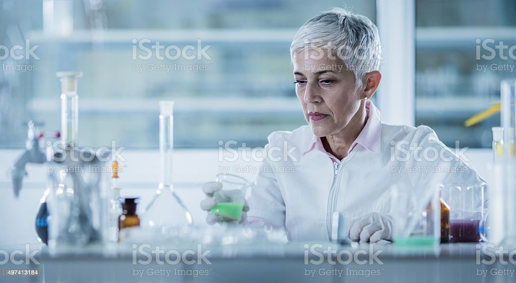 Panoramic view of a female chemist working in laboratory. stock photo