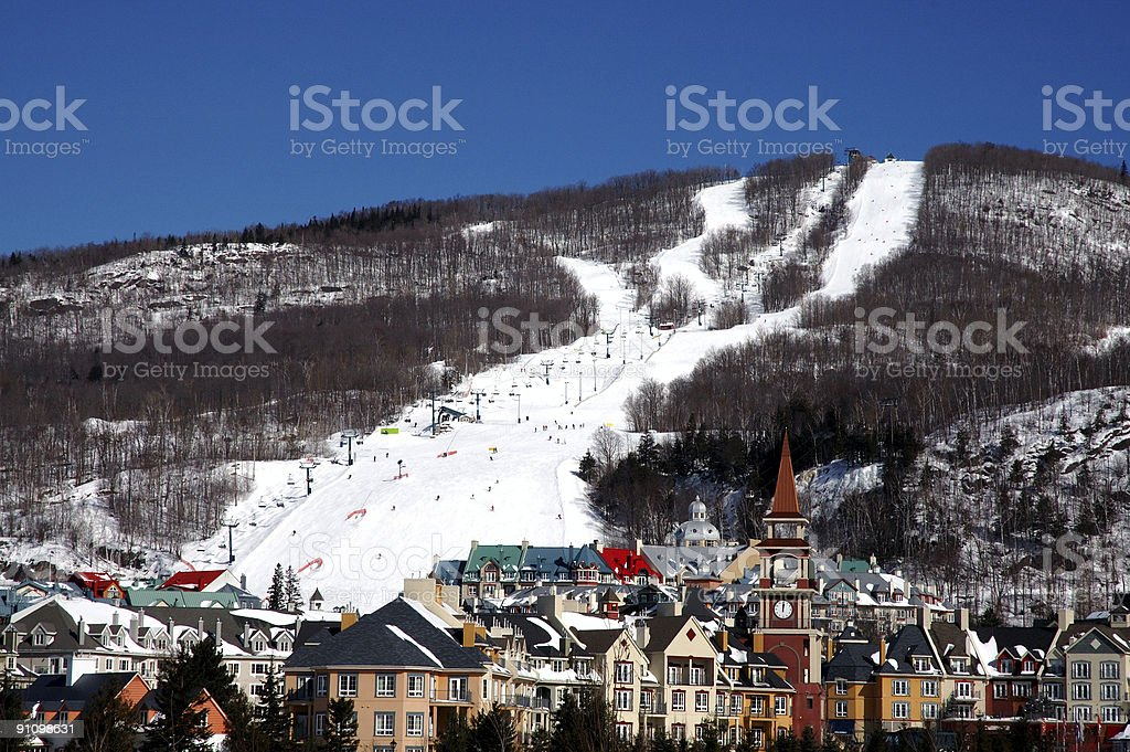 Panoramic view of a ski hill with village below stock photo