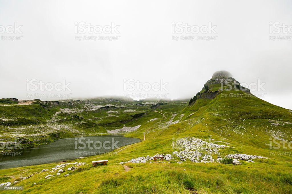 panoramic view of Alps mountains with lake, in the clouds stock photo
