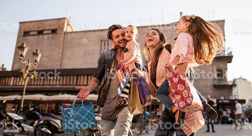 Panoramic view of cheerful family having fun in shopping. stock photo