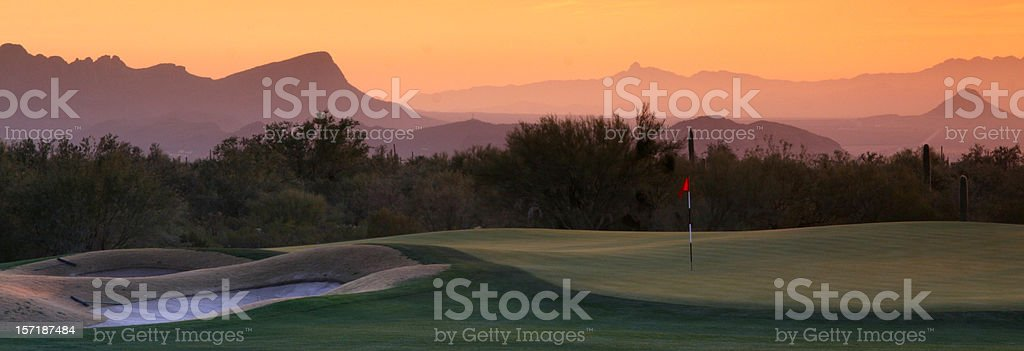 Panoramic view of desert golf course under hazy orange sky. stock photo