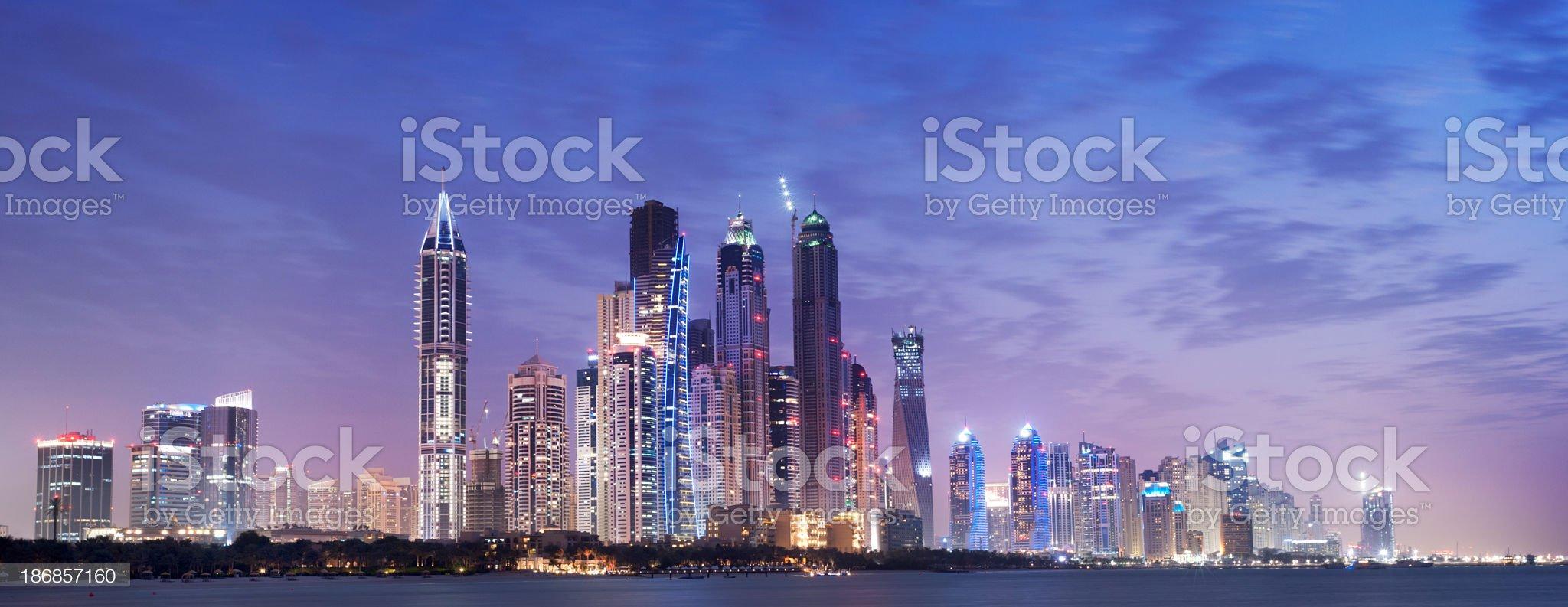 Panoramic View of Illuminated Dubai Marina Skyline at Night UAE royalty-free stock photo
