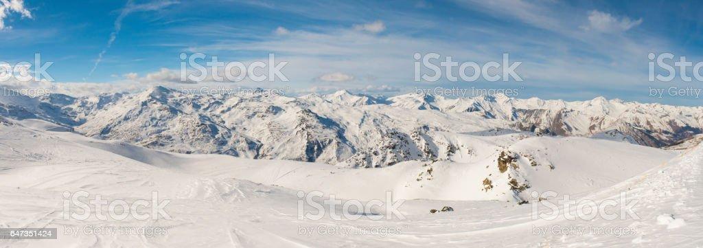 Panoramic view of mountain range with ski piste stock photo