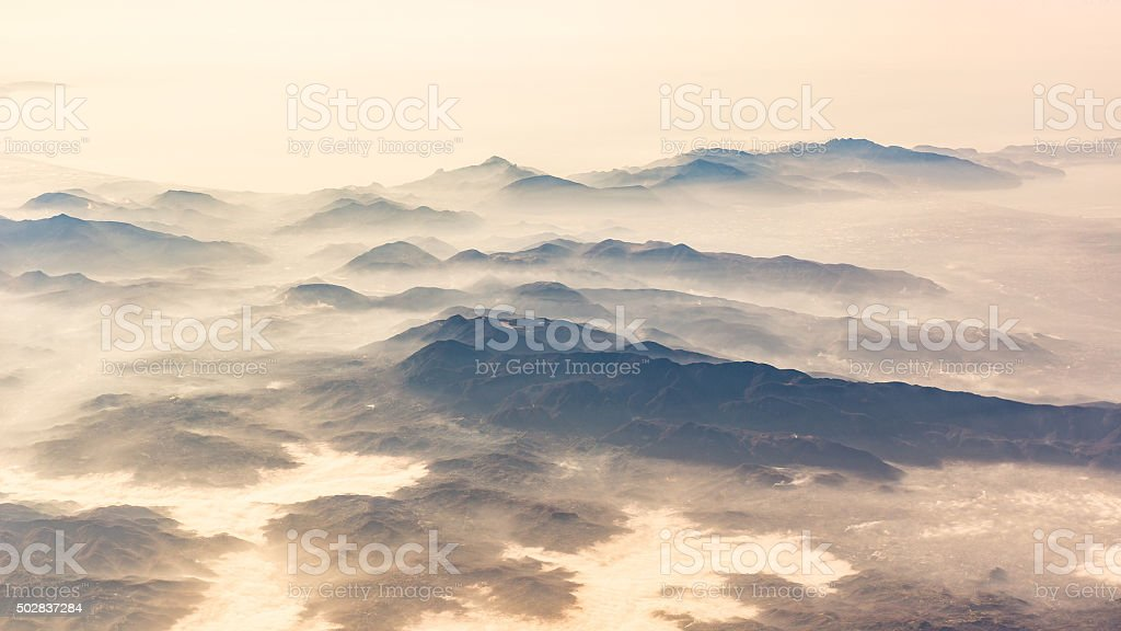 Panoramic view of mountains and clouds from airplane stock photo