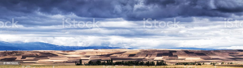 Panoramic view of plowed field under cloudy sky stock photo