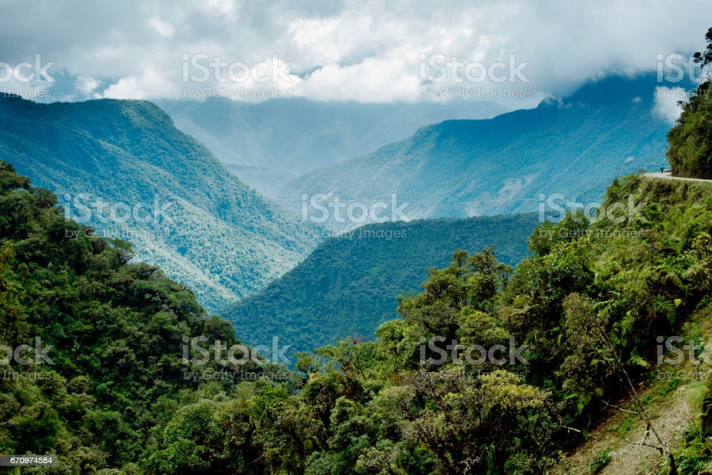 Panoramic view of the mountainous landscape of North Yongas and a cyclist on the Death Road on the far right, Bolivia stock photo