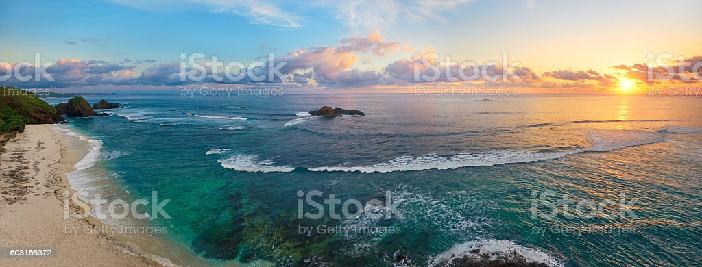 Panoramic view of tropical beach with surfers at sunset. stock photo