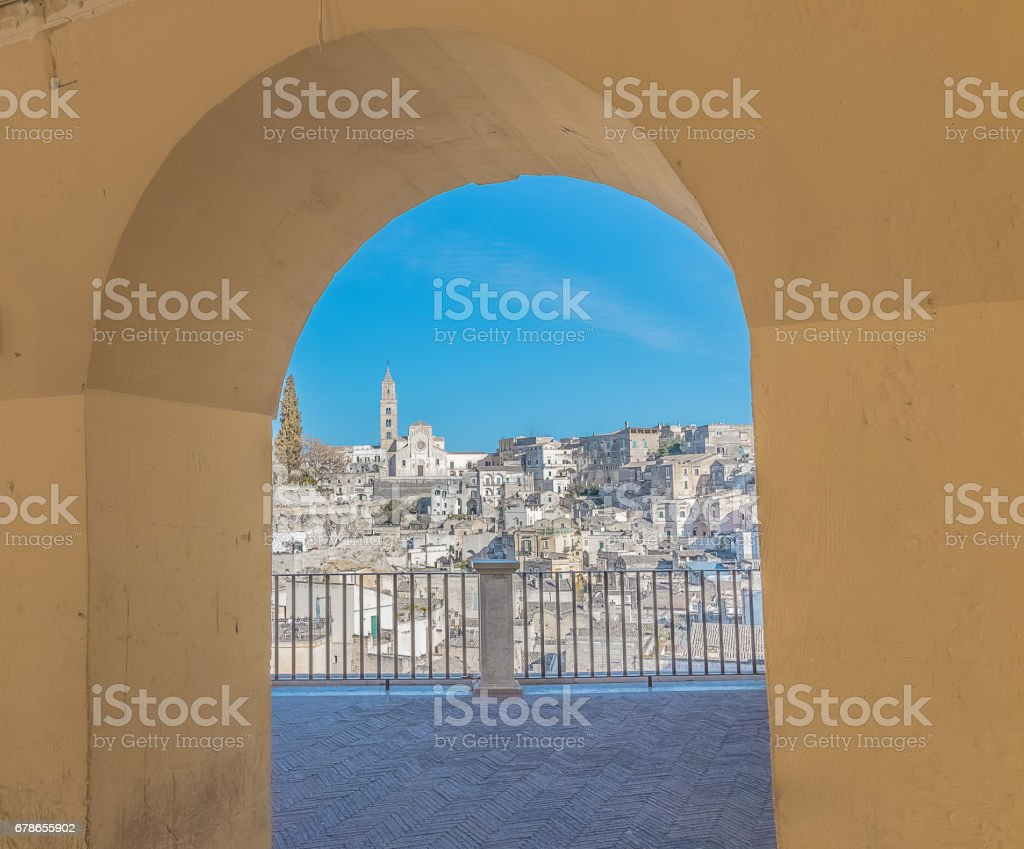 panoramic view of typical stones (Sassi di Matera) and church of Matera under arcade stock photo