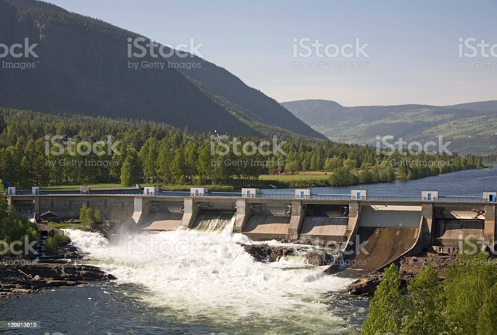 Panoramic view of water spilling over a dam at a power plant stock photo