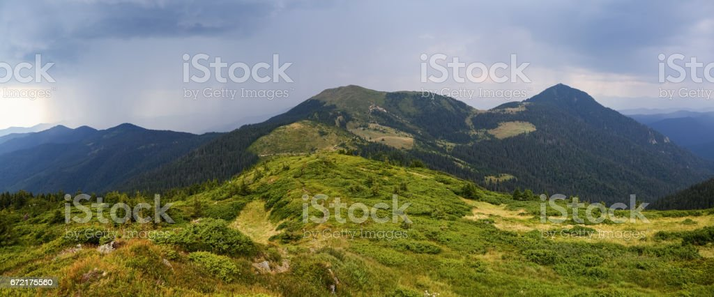 Panoramic view on high mountains and stormy  sky with clouds is opened from the green marvelous lawn. stock photo