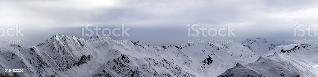Panoramic view on high snowy mountains and sunlight storm sky stock photo