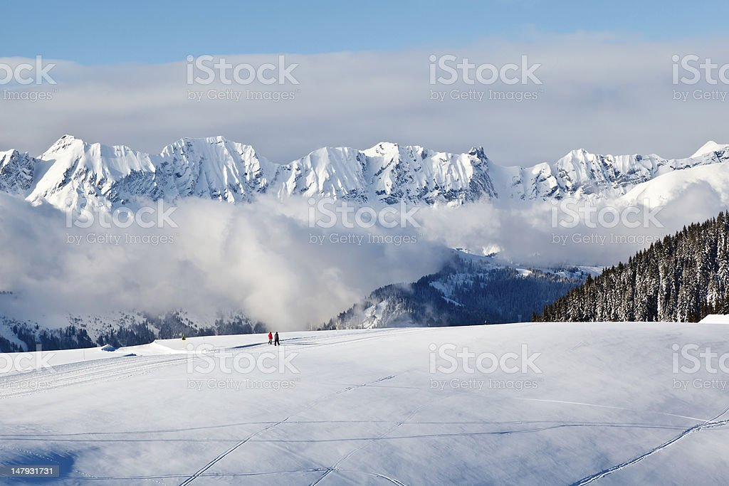 Panoramic View on Mountains and Two People Trekking in Alps royalty-free stock photo