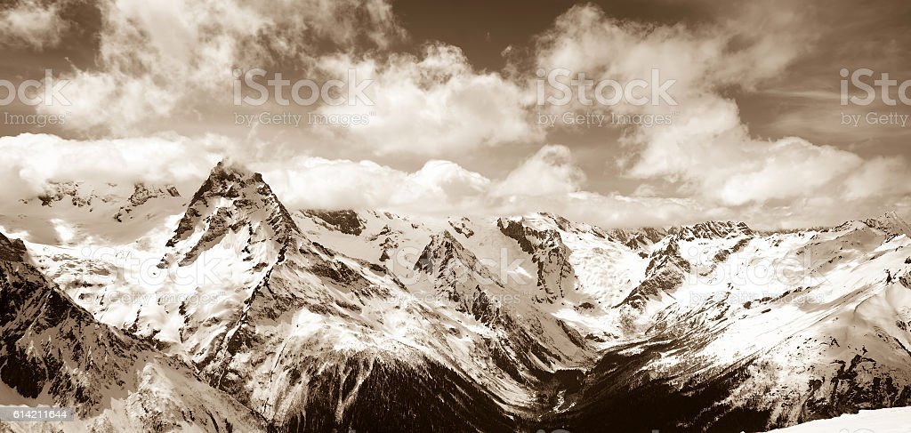 Panoramic view on winter snow mountain in clouds stock photo