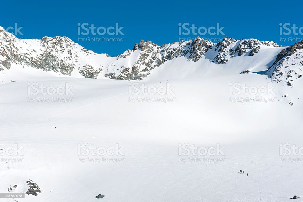 Panoramic view over a snowy slope with hikers stock photo