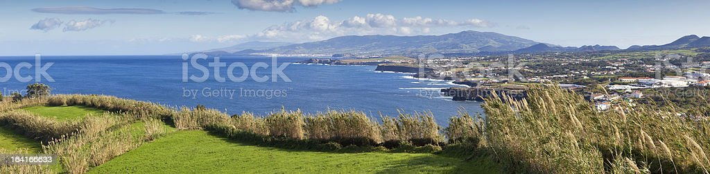 Panoramic view to the field, town and mountains royalty-free stock photo