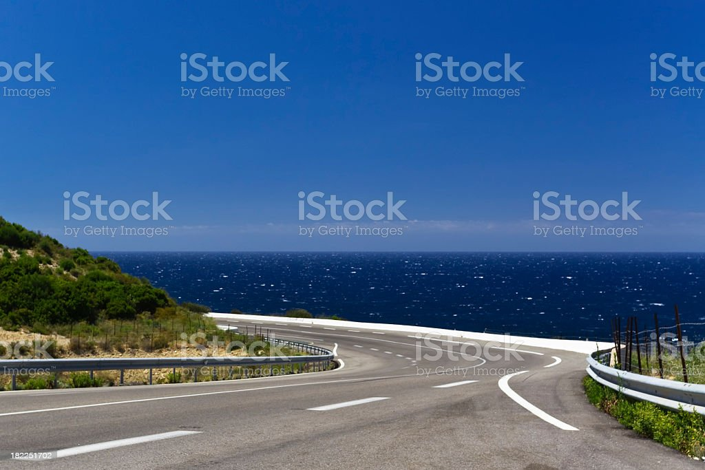 Panoramic winding road that goes along a body of water stock photo