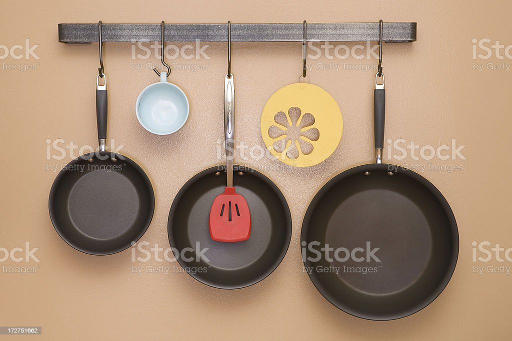 Pans and Utensils Hanging on Kitchen Wall stock photo