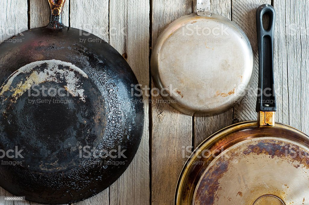 pans hanging on a wooden wall stock photo