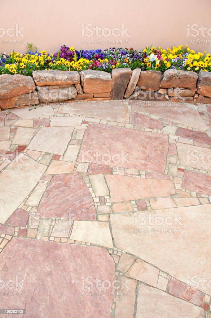 Pansy Flowers in Rock Garden with Flagstone Paving Stone stock photo