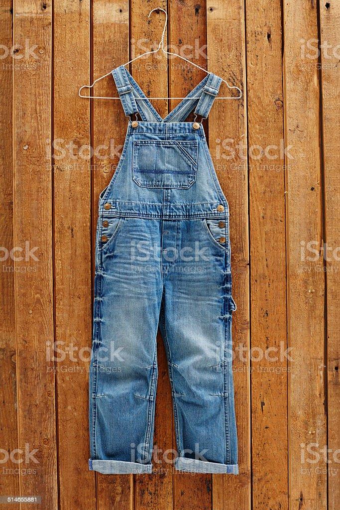 pantsPair of denim dungarees hanging against wooden wall stock photo