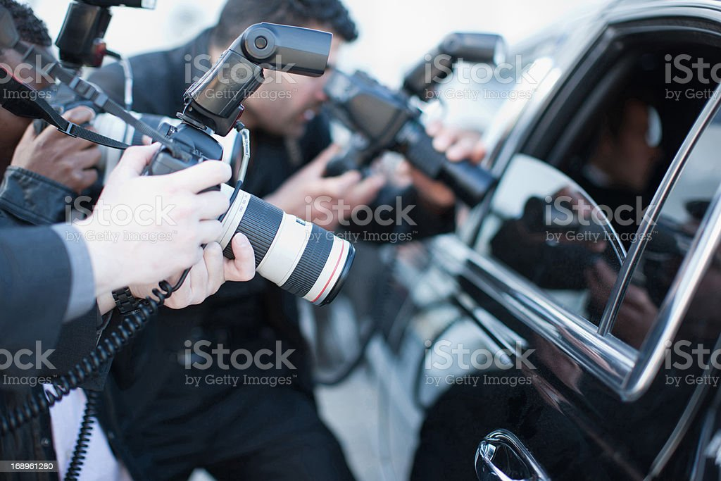 Paparazzi holding camera lens to car window stock photo