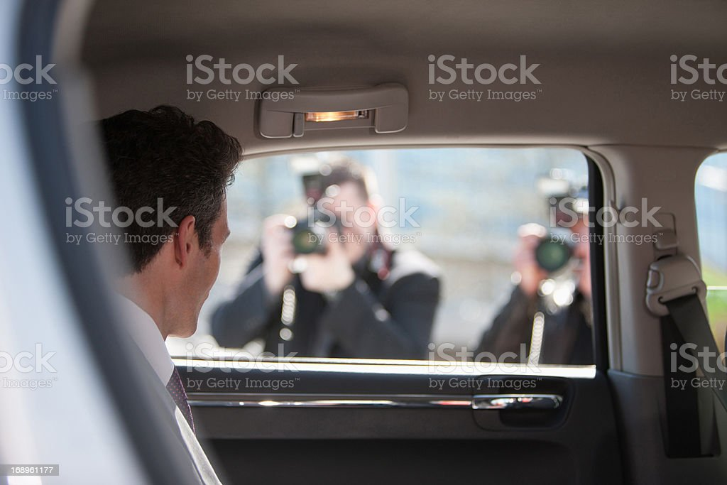 Paparazzi taking pictures of politician in car royalty-free stock photo