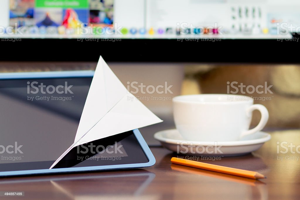Paper airplane on tablet in the home office royalty-free stock photo