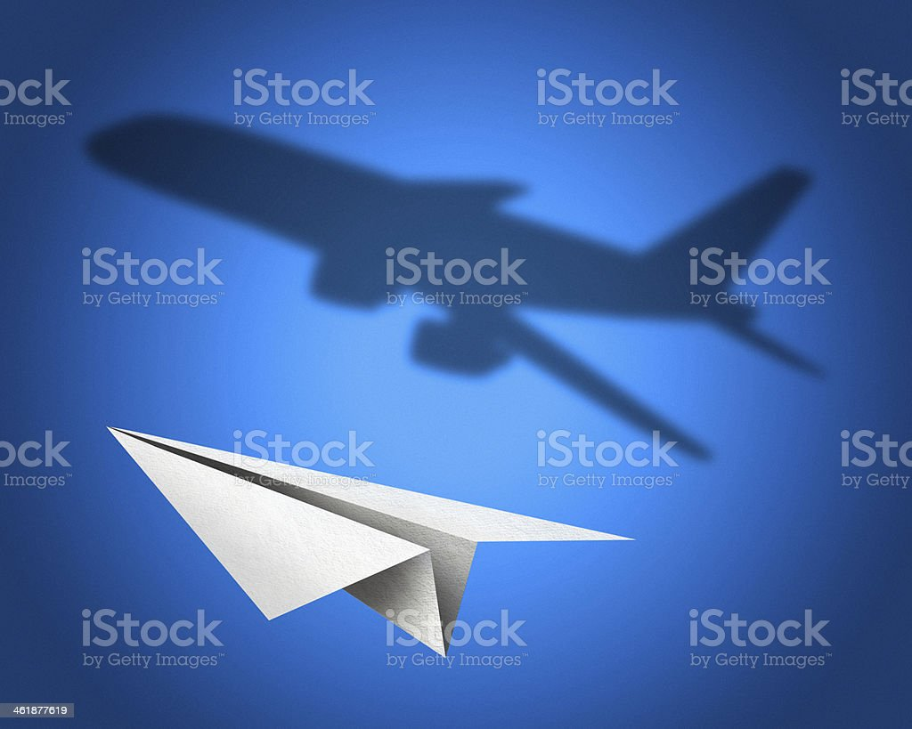 Paper airplane with a shadow of jetliner stock photo