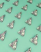 Paper airplanes made out of money on the green background