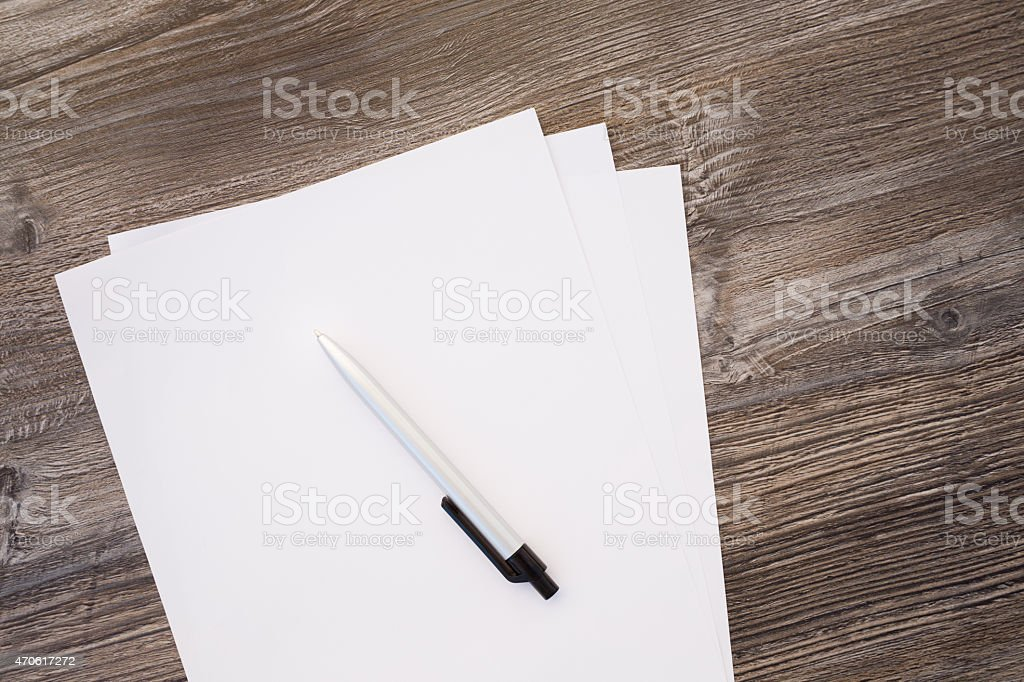 paper and pencil on wooden table stock photo