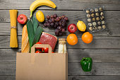 Paper bag full of different groceries on wooden table