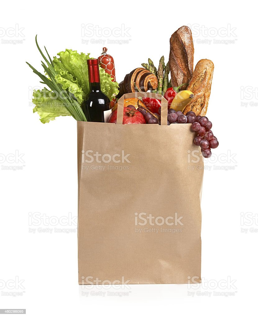 A paper bag full of groceries on a white background stock photo