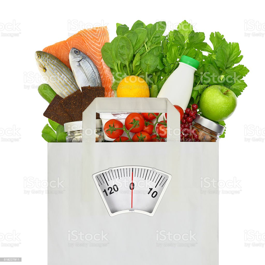 Paper bag full of groceries with weighing scale stock photo