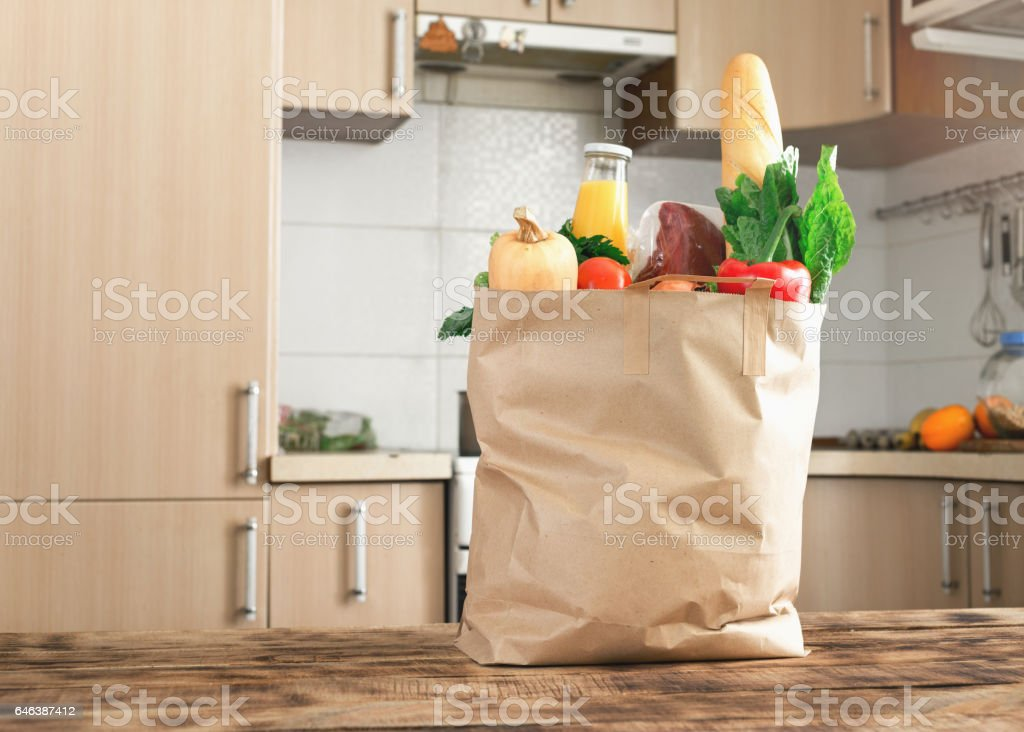Paper bag full of healthy food on a wooden table in the kitchen stock photo