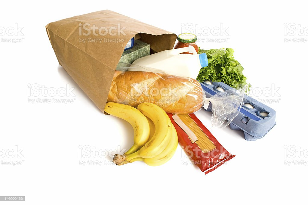 Paper bag of groceries scattered on white background stock photo