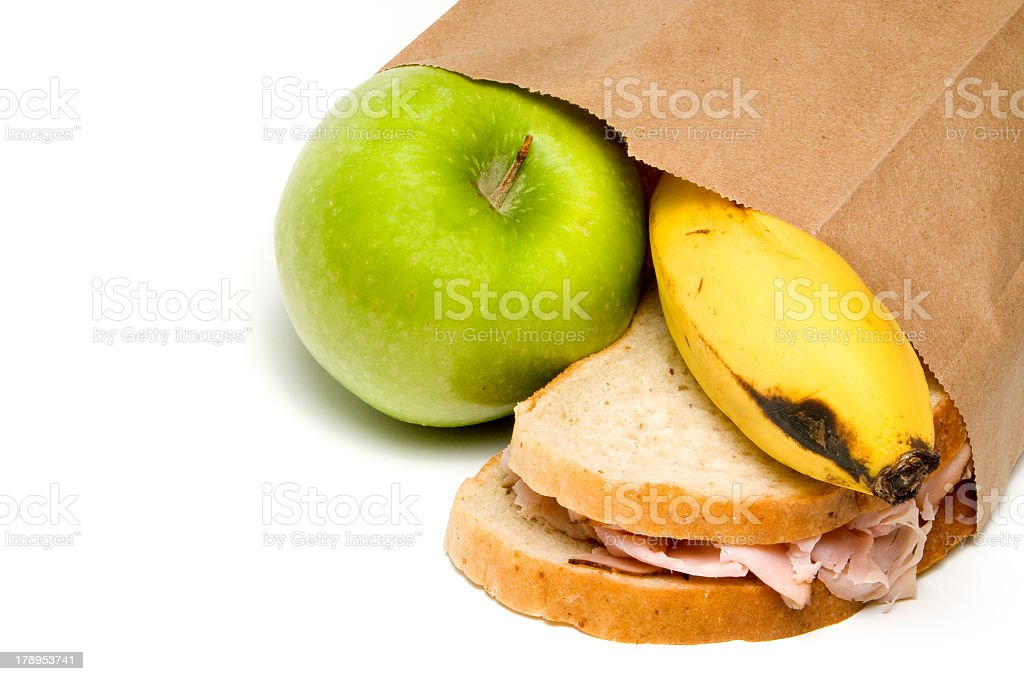 Paper bag with an apple, sandwich, and banana falling out royalty-free stock photo