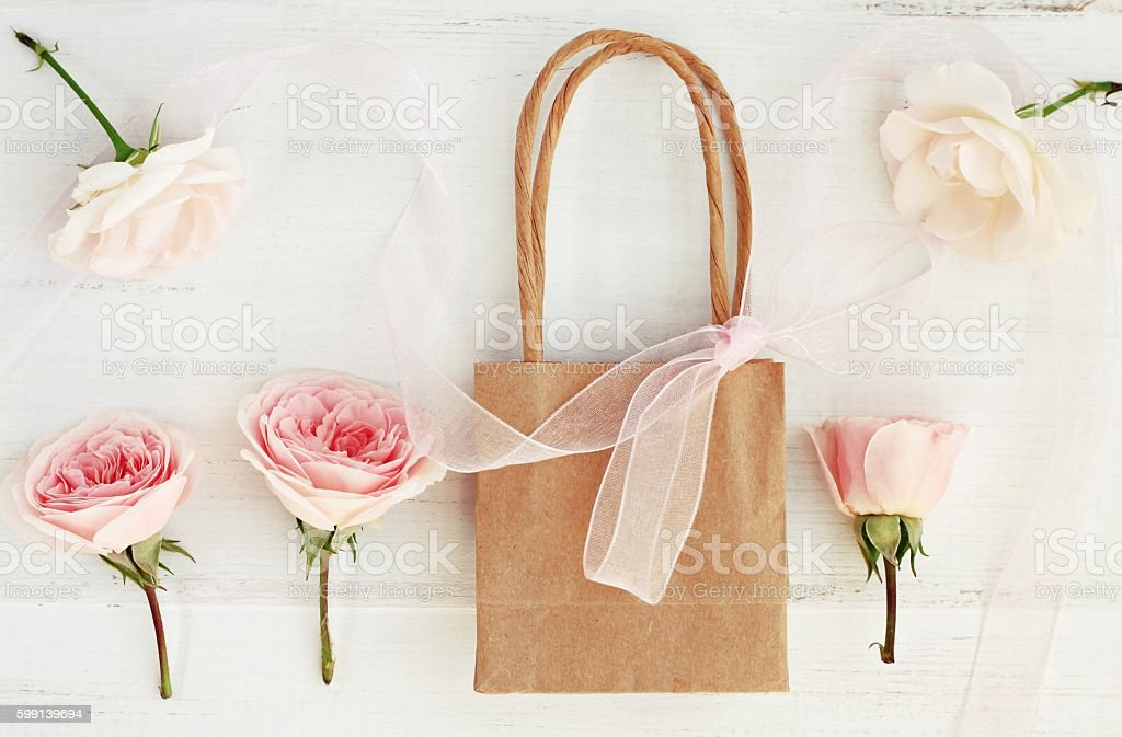Paper bag with bow and roses. Creamy toned present. stock photo