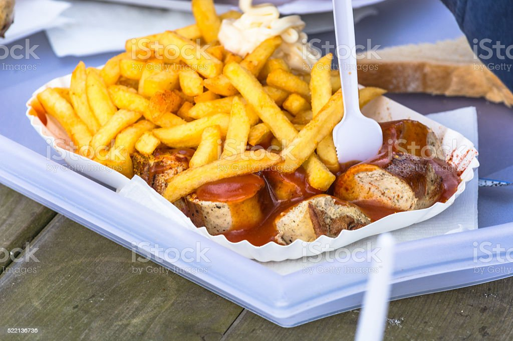 Paper bag with curried sausage and French fries stock photo