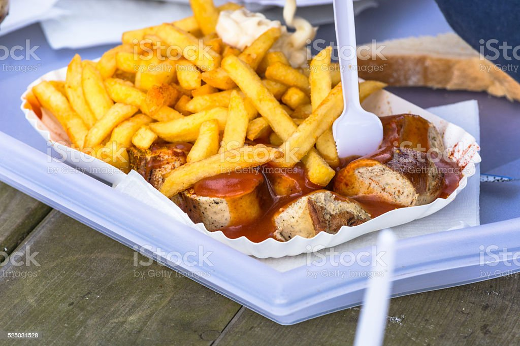 Paper bag with currywurst and French fries stock photo
