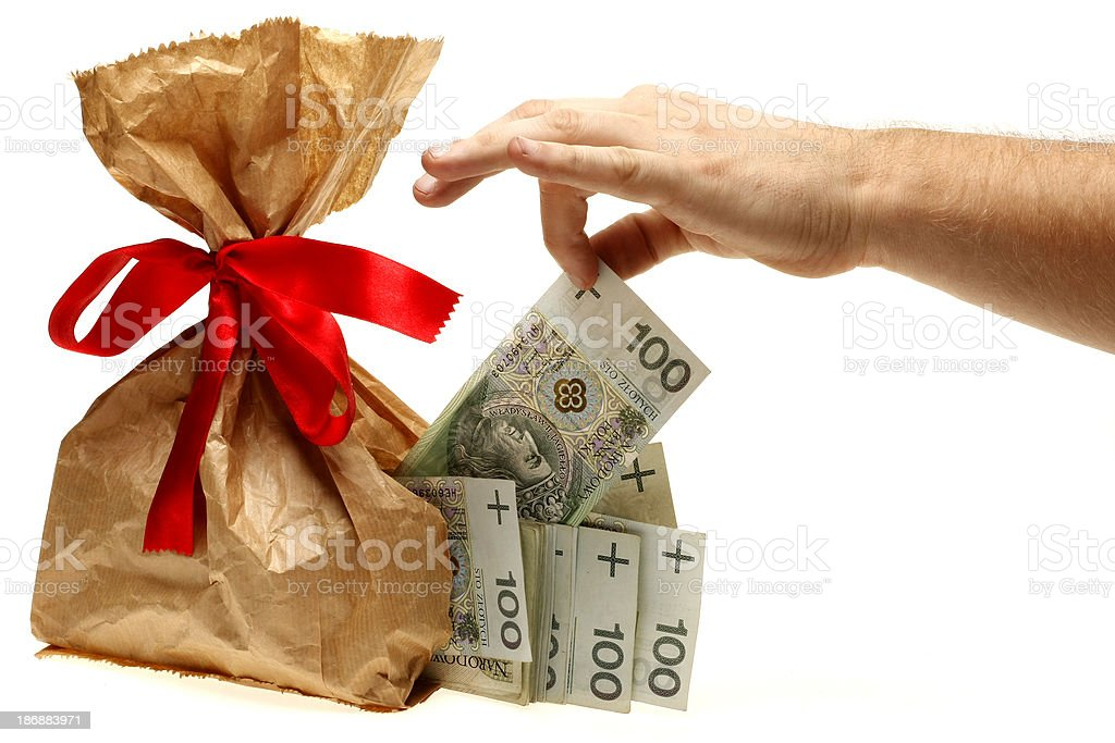 Paper bag with red ribbon banknotes falling out through hole royalty-free stock photo
