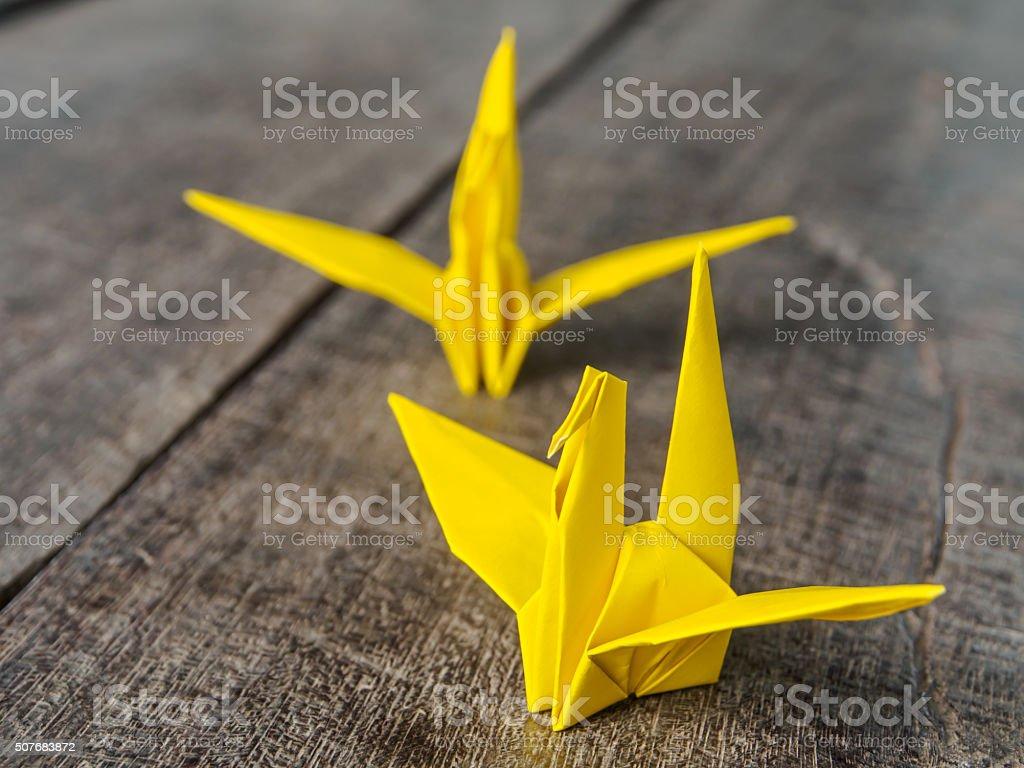 Paper bird  yellow on wooden stock photo