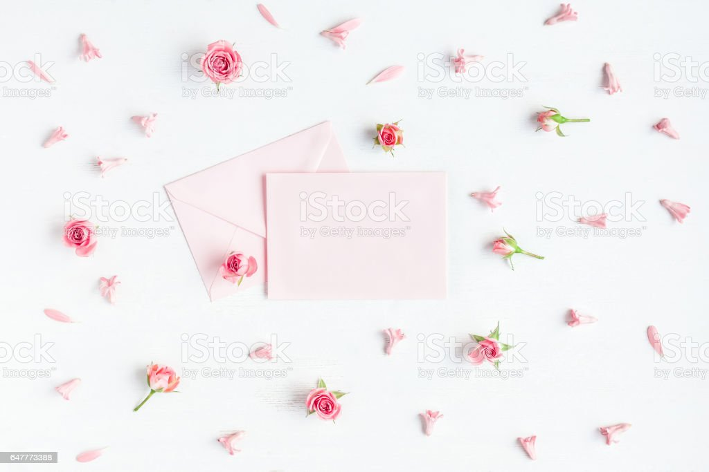 Paper blank and pink flowers on white background. Mockup stock photo