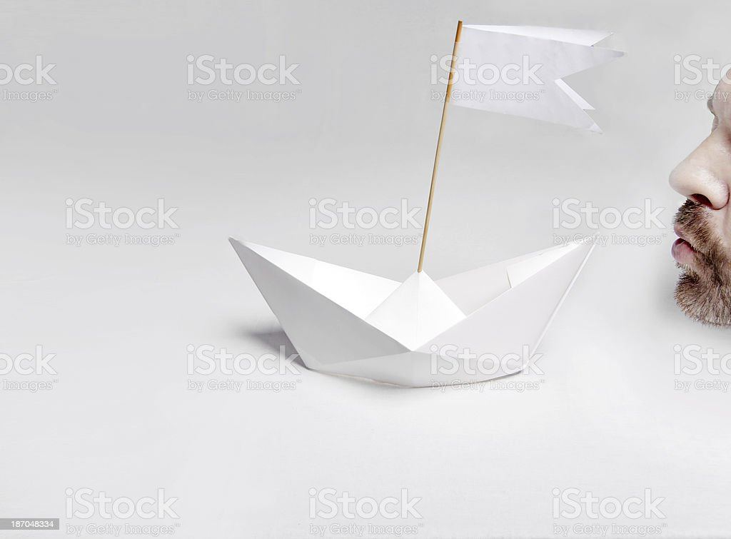 Paper boat begins the race with man blowing on sails stock photo